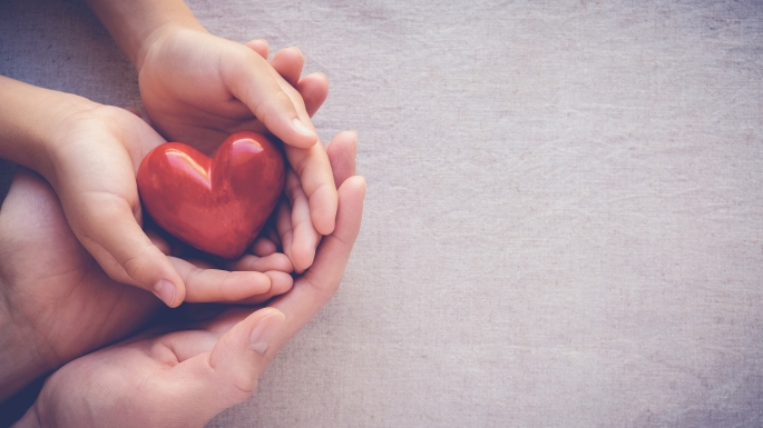 adult and child hands holding red heart health care love and family concept